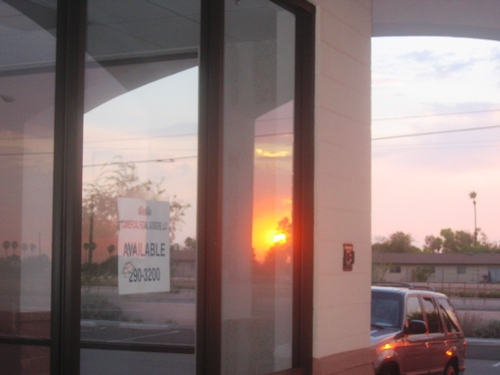 Monday's sunset reflected in an unrented storefront.